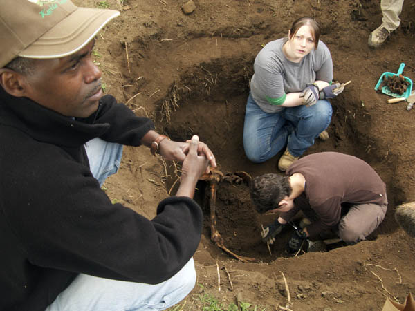 UIndy grad student Amandine Eriksen, upper rights, works with anthropologist Shannon C. McFarlin of The George Washington University and veterinarian Antoine Mudakikwa of the Rwandan Office of Tourism and National Parks to excavate a mountain gorilla skeleton.