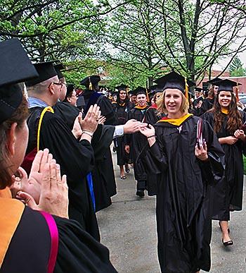 Faculty members applaud graduates after the 2013 undergrad ceremony.