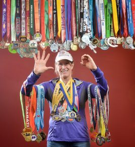 Dr. Kathy Stickney (Chemistry Department) has successfully completed marathons in all 50 states. She's received various medals from the runs which she gathered for this environmental portrait on January 11, 2017. (Photo by D. Todd Moore, University of Indianapolis)