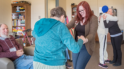 Student Tori Zimmerman dances during a therapy session. Prof. Jan Schreibman is on the right. At Still Waters Adult Day Care facility in Indianapolis.