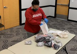 A student assembles care packages for a service project to support the University Heights neighborhood during the coronavirus pandemic.
