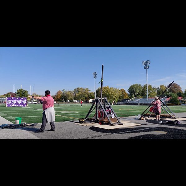 President Rob Manuel, left, and Dean of Students Kory Vitangeli, right, put the trebuchets to the test!